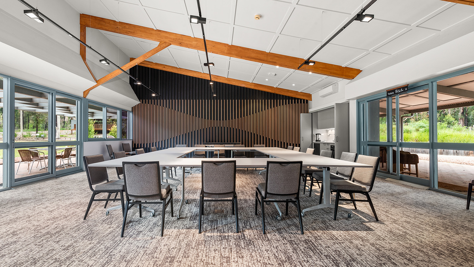 A conference style desk and seating arrangement in the Banksia Room