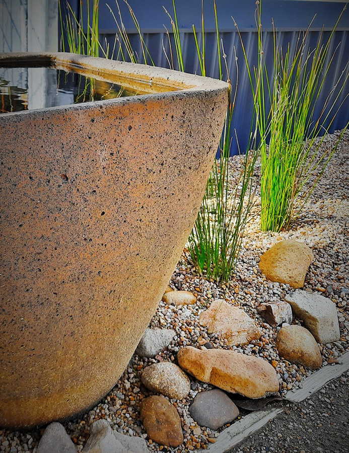 Close up potted water feature and garden stones