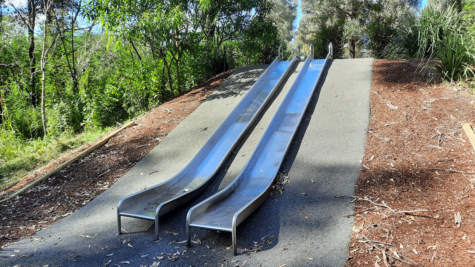 Two outdoor slides on a hillside